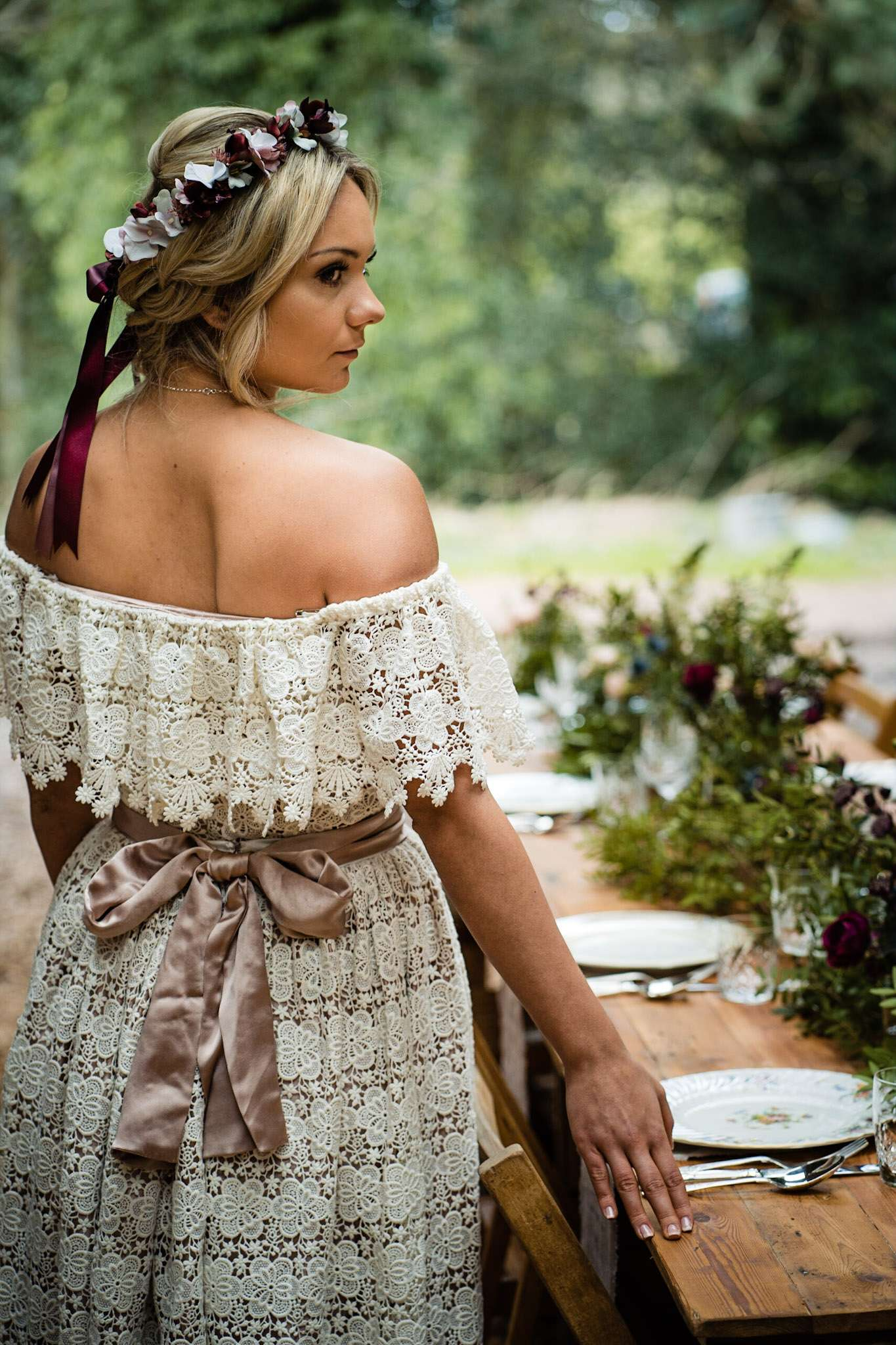 A bride posing at the wedding breakfast table at Patricks Barn, West Sussex
