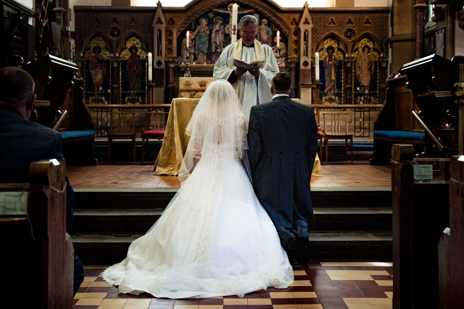 A bride and groom kneeling before a vicar in church