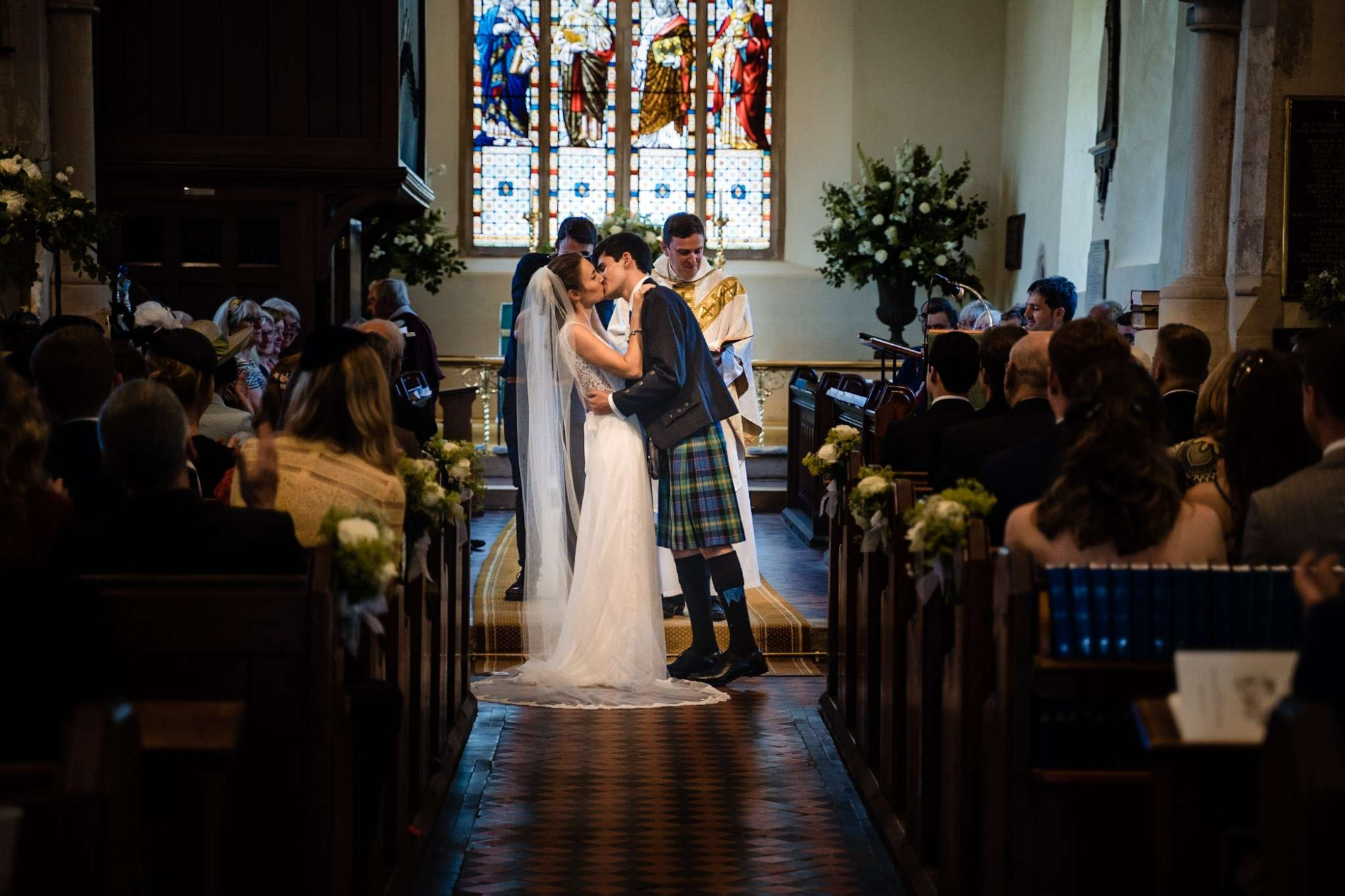 A bride and groom have their first kiss in a church