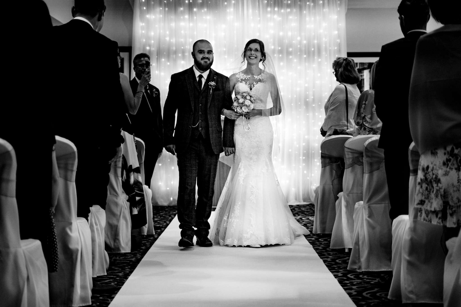 Newly married walking up the aisle after getting married at Frimley Hall Hotel