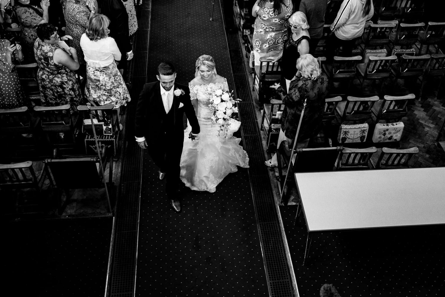 Newly married walking up the aisle of a church after getting married