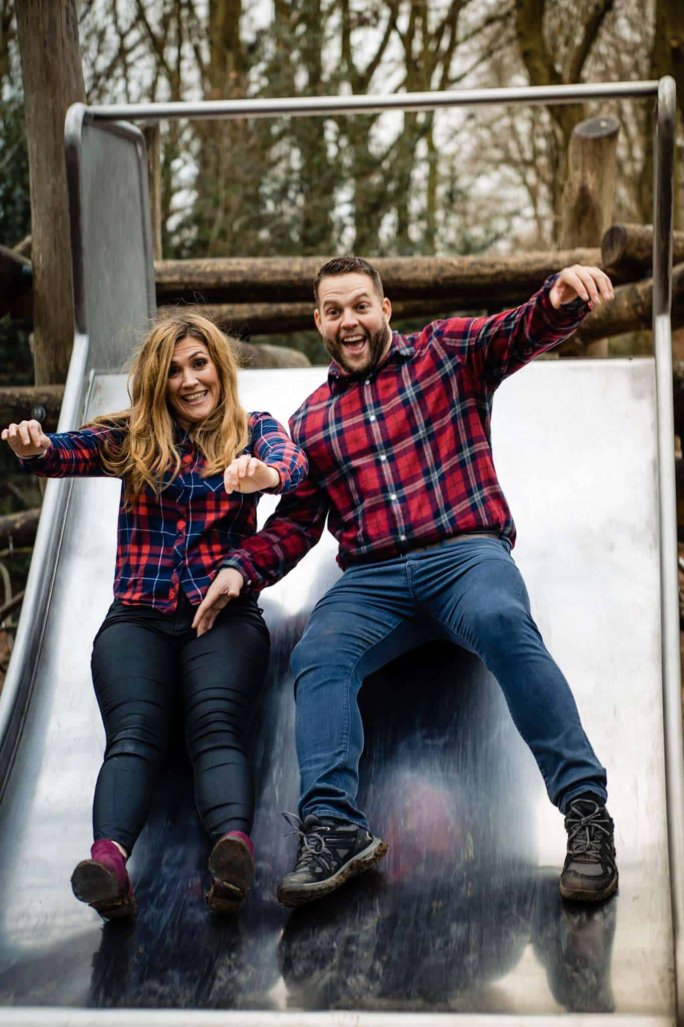 An engaged couple having fun on a slide during their engagement shoot