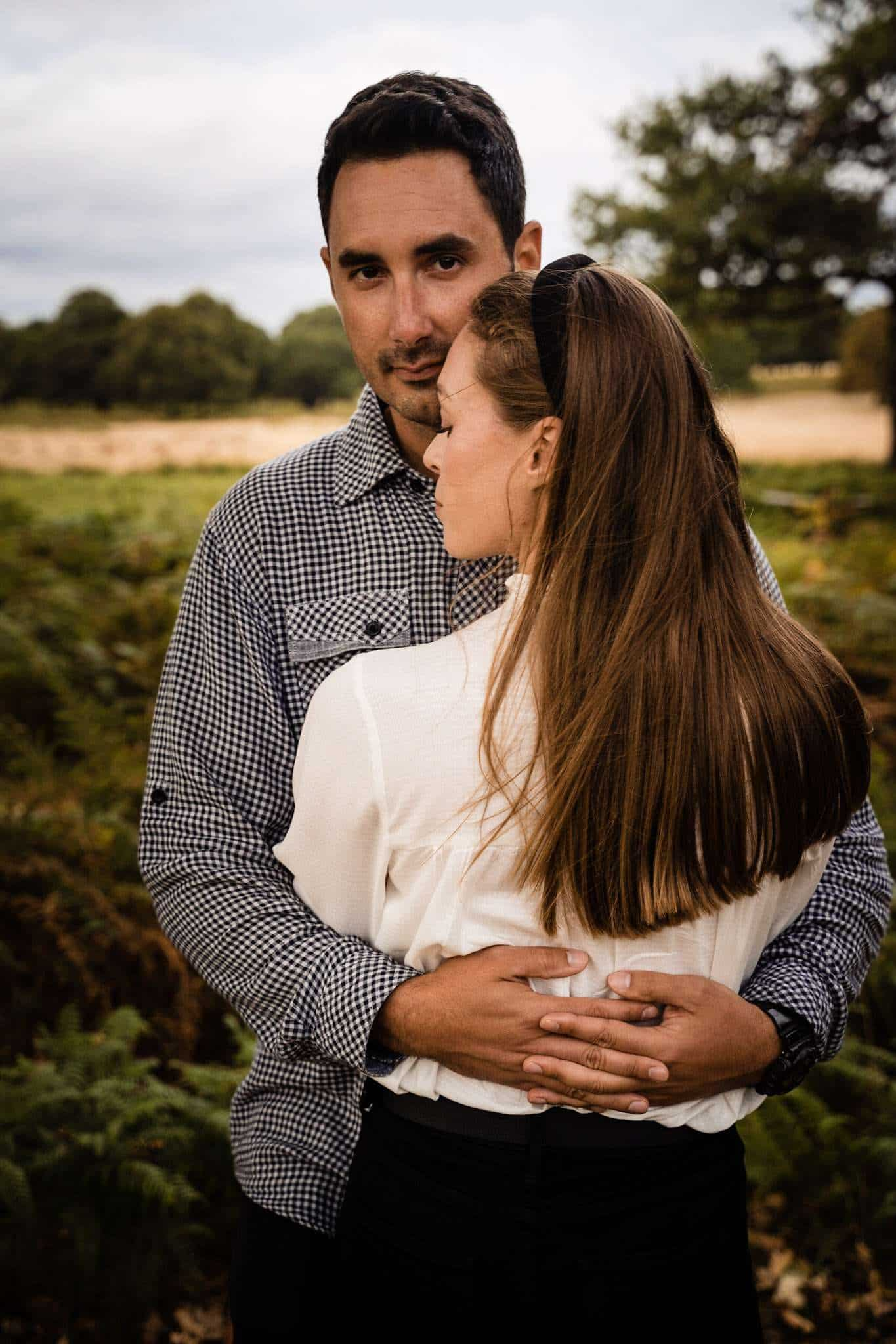 An engaged couple share an embrace in Richmond Park