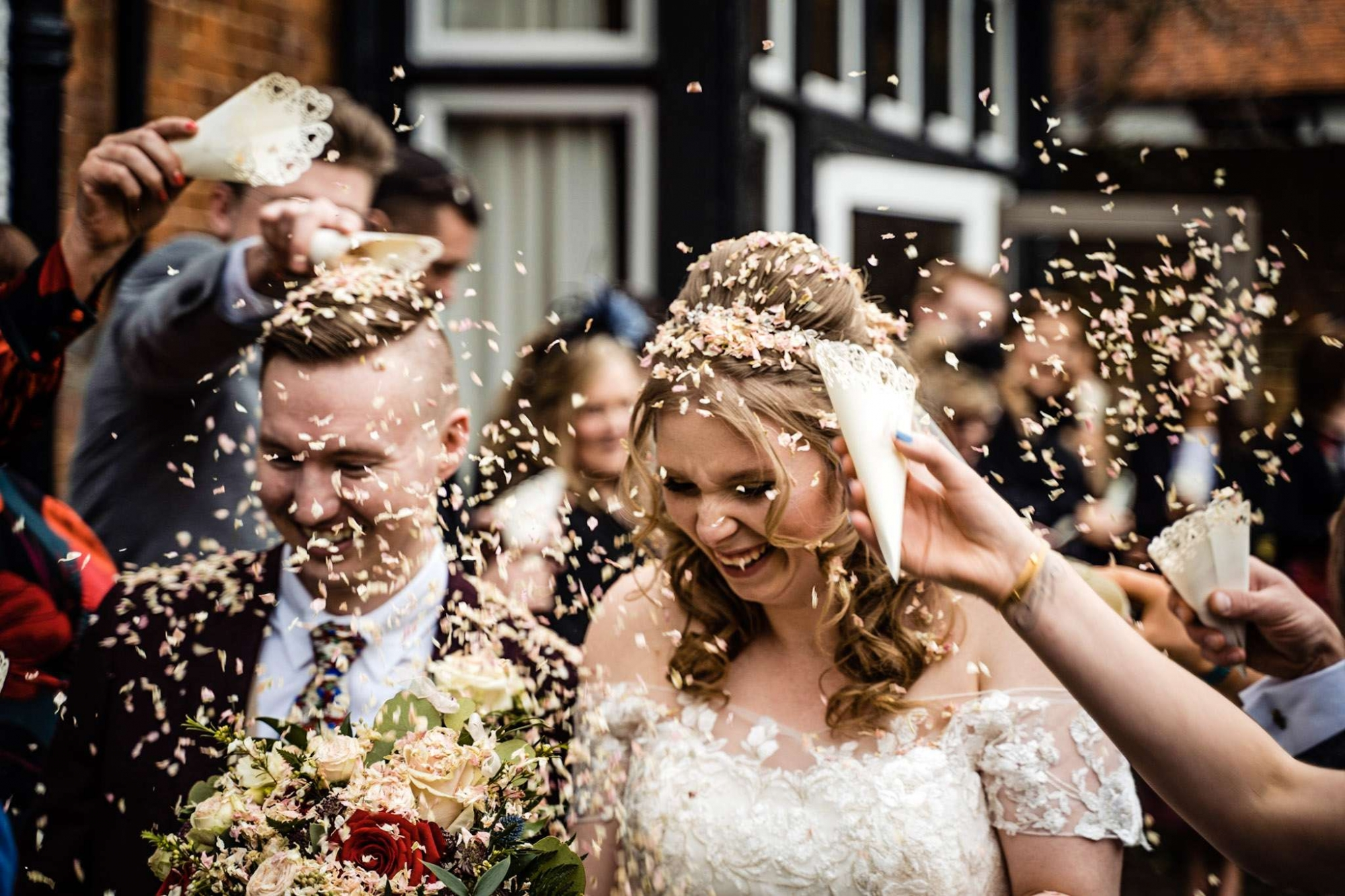 A bride and groom having confetti thrown over them at the Olde Bell Inn, Maidenhead