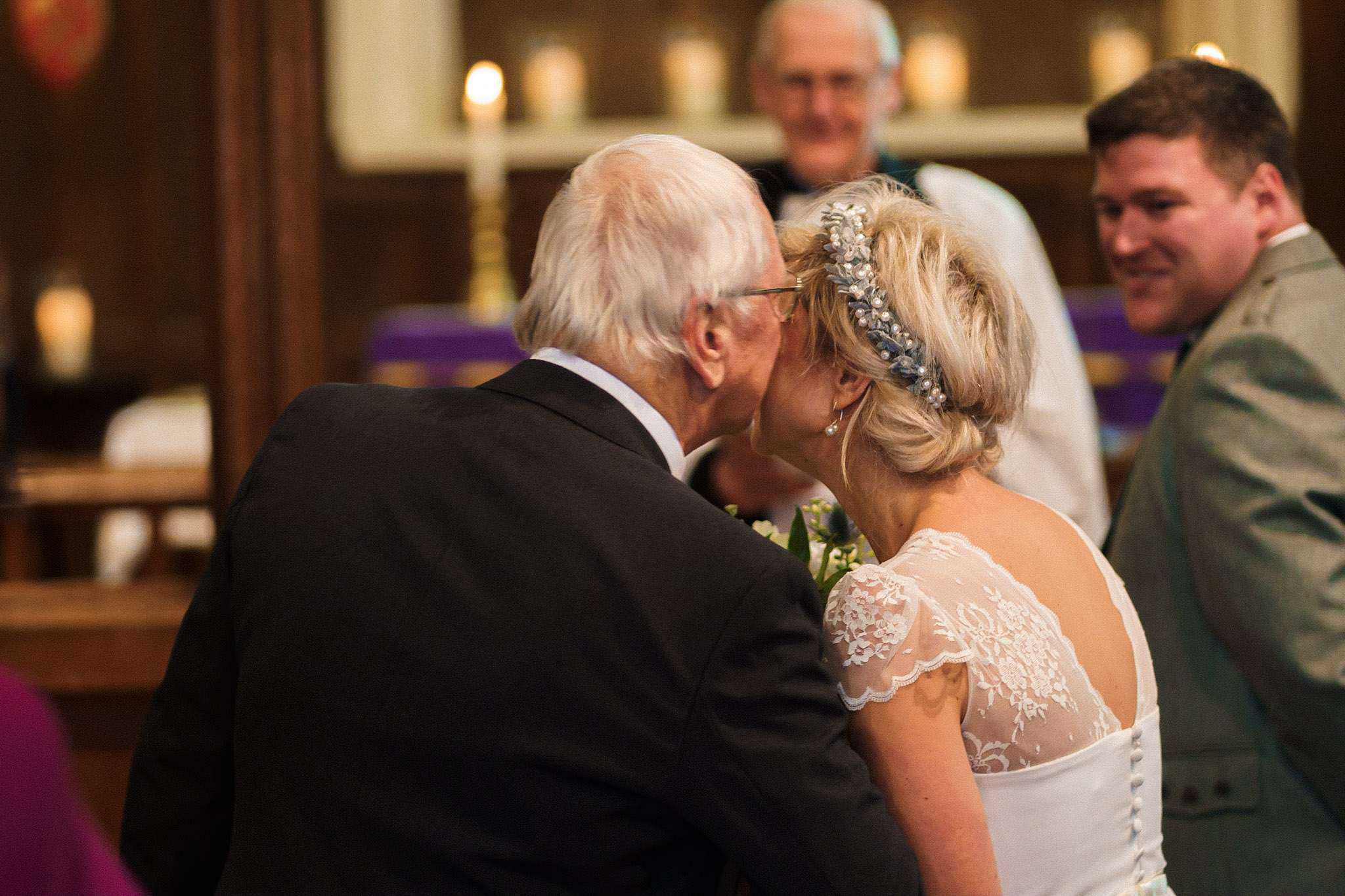 The father of the bride kisses her cheek before she gets married