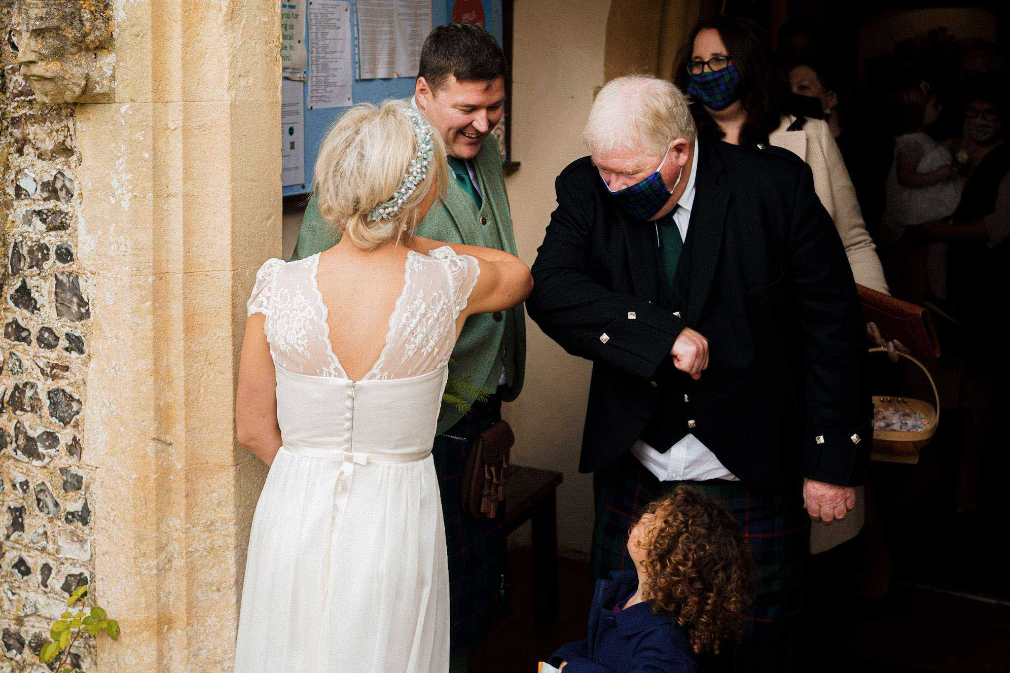 A Covid-19 safe greeting between a bride and her guests