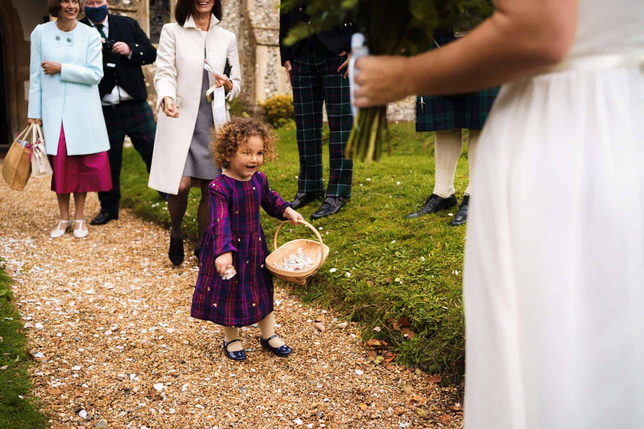 A young guest at a wedding is throwing confetti over the bride and groom