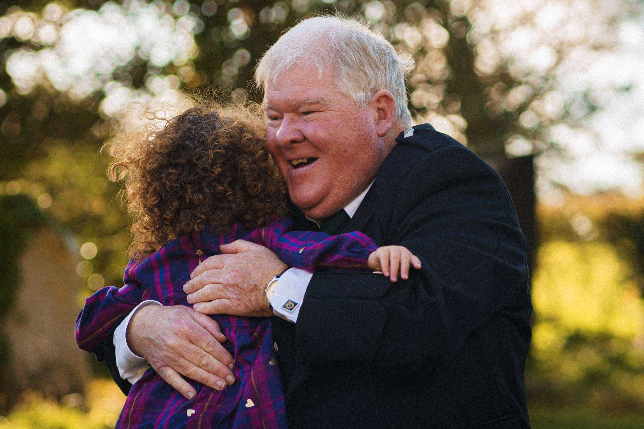 A grandfather hugging his granddaughter at a wedding ceremony