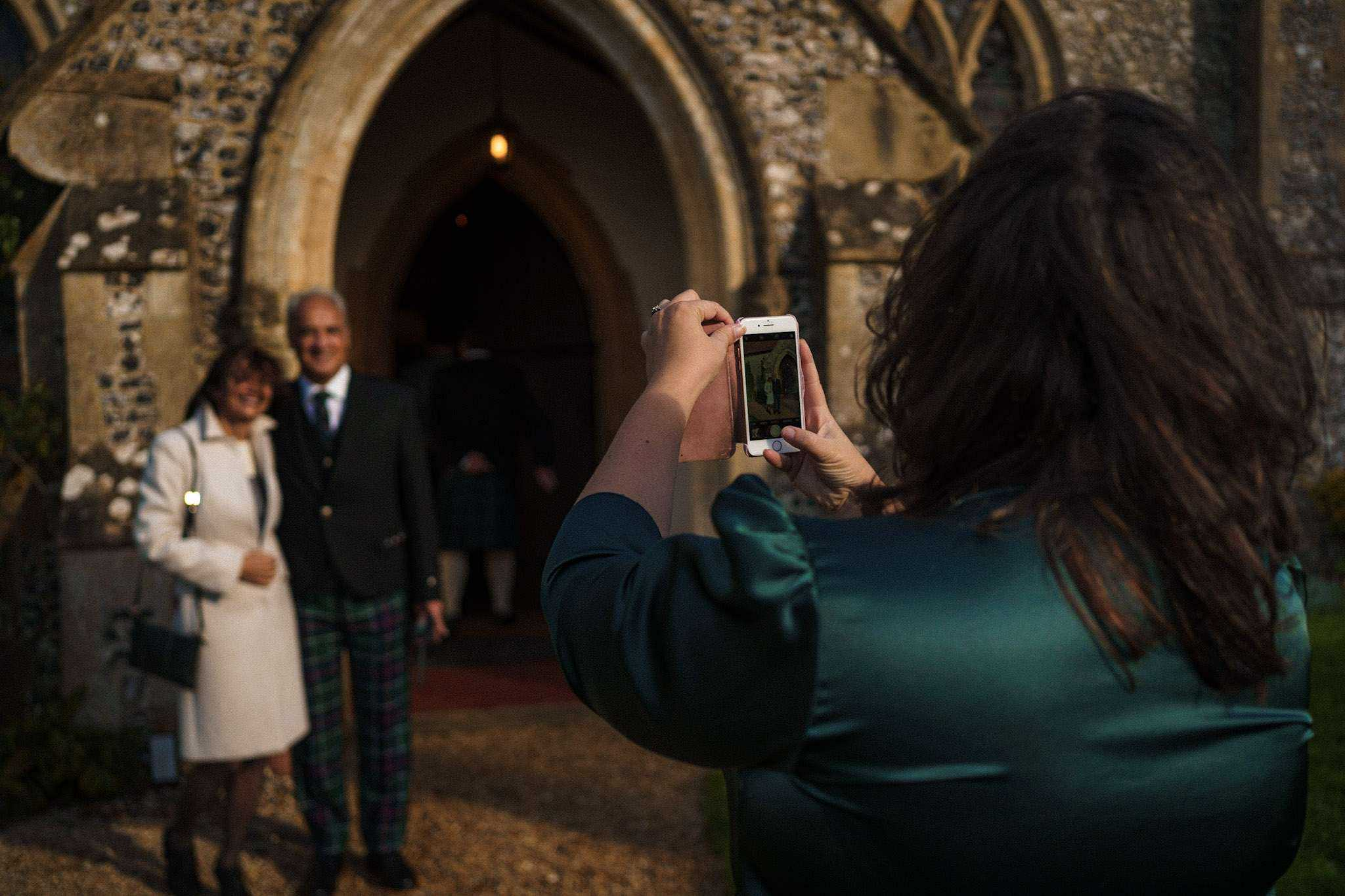 A wedding guest taking a photo before the bride arrives