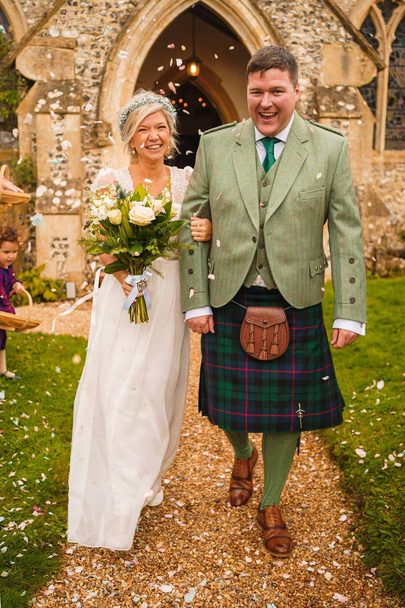A couple walk out of church after getting married and have confetti thrown over them