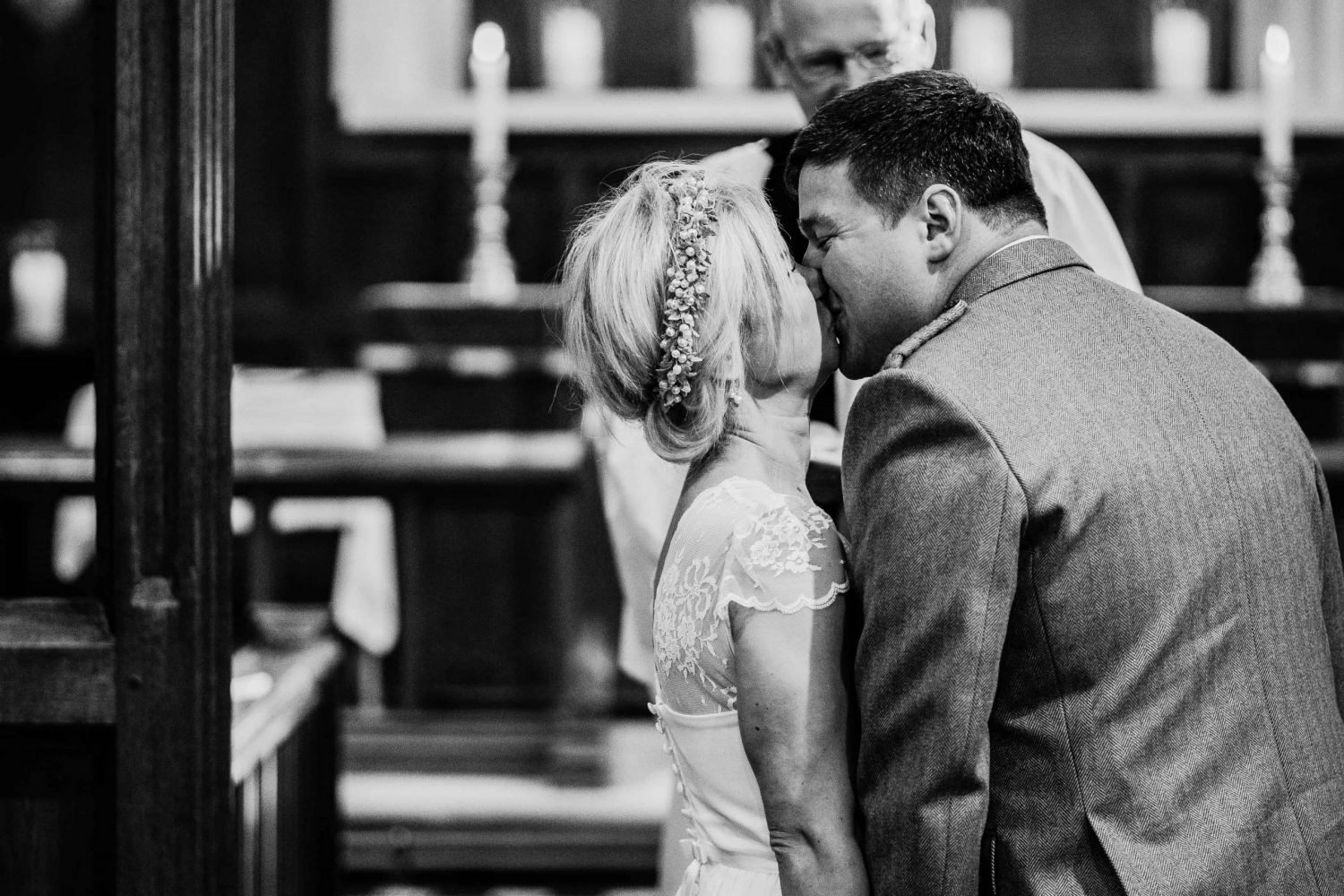 A newly married couple share their first kiss in church