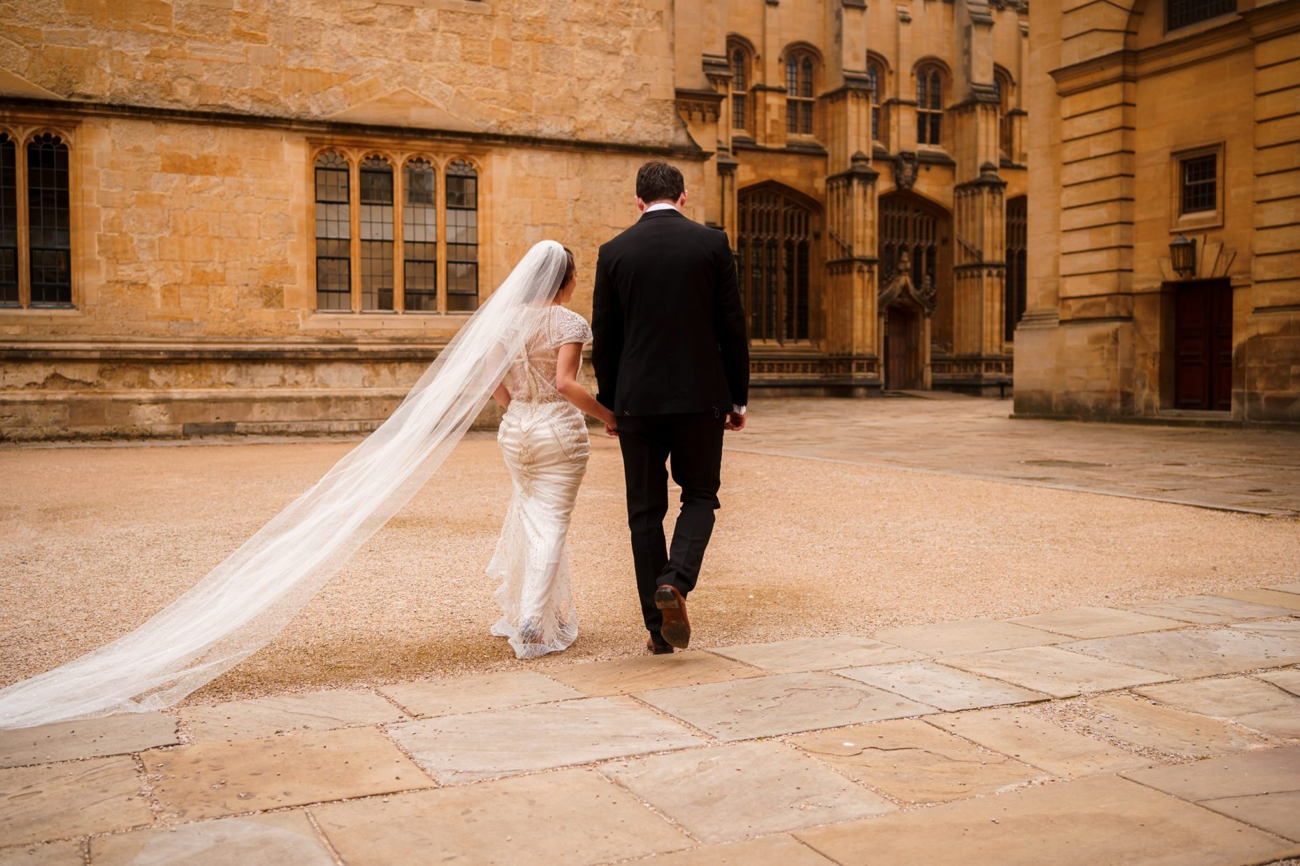 Bride and groom walking hand in hand toward the Bodleian Library, Oxford