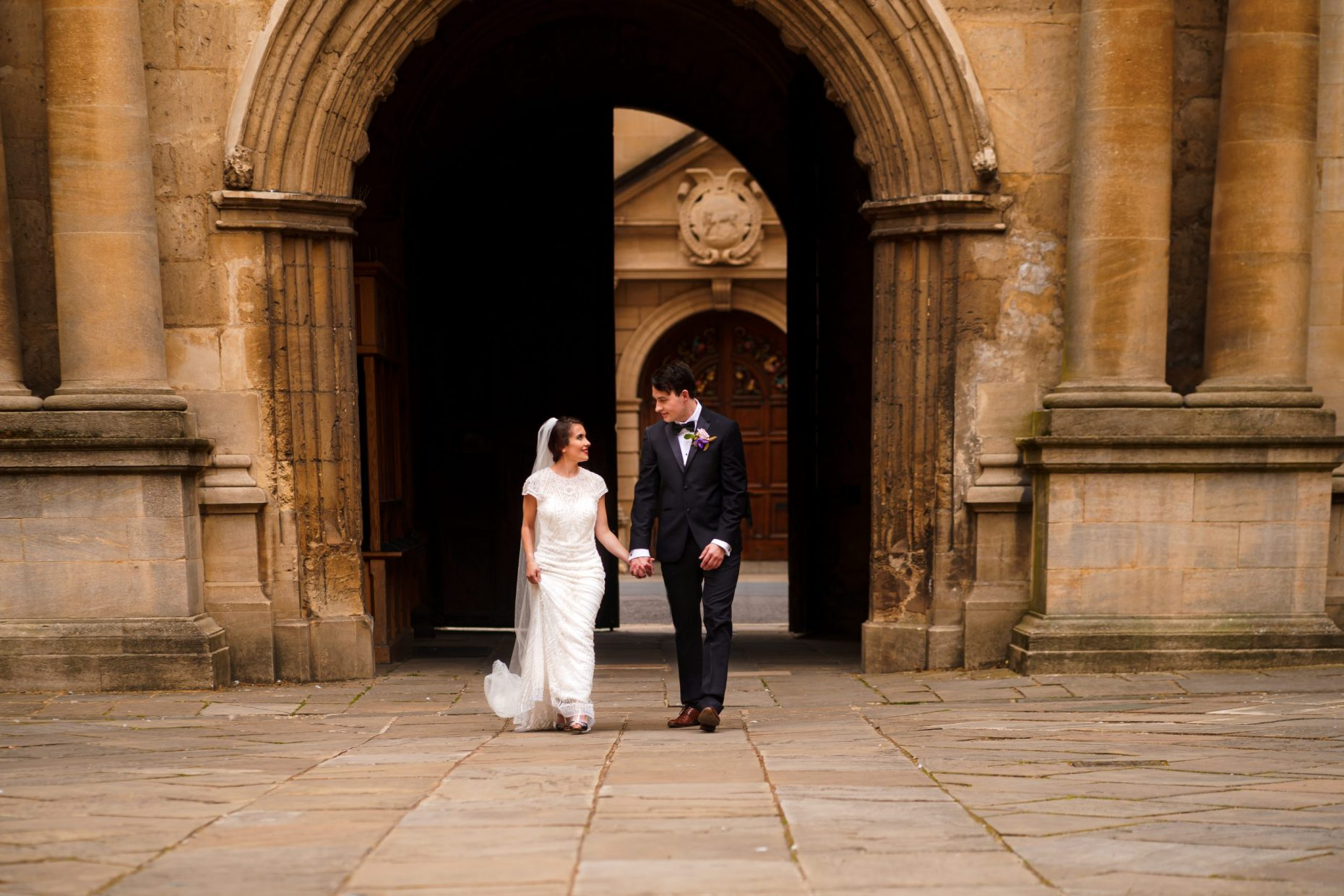Bride and groom walking hand in hand in the Bodleian Library, Oxford